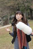 Young Asian woman eating cotton candy in outdoor.