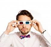 Serious young man in a red and cyan bow tie wearing 3d glasses and peering earnestly through them at