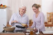 foto of pancake flip  - Mother and daughter cooking crepes - JPG
