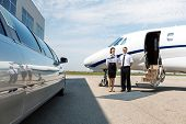 stock photo of neat  - Flight attendant and pilot standing neat limousine and private jet at airport terminal - JPG