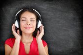 Music in headphones. Beautiful young Asian woman with her eyes closed in bliss listening to music we