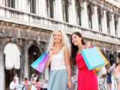 Shopping women - girl shoppers holding shopping bags in Venice. Portrait of beautiful girlfriends sm