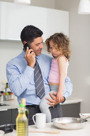 stock photo of half-dressed  - Well dressed father with daughter preparing food while on call in the kitchen at home - JPG