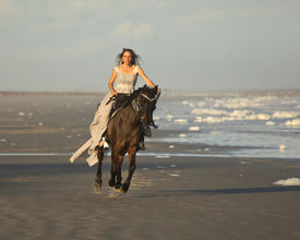 picture of bareback  - woman in medieval dress riding arabian horse on beach - JPG