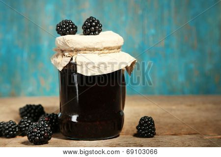 Tasty blackberry jam and fresh berries, on wooden background