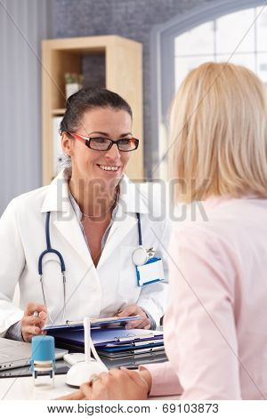 Happy female brunette doctor with glasses at medical office with patient, smiling, clipboard in hand, wearing stethoscope and lab coat.