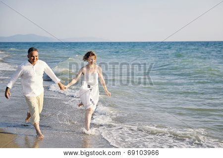 Happy Couple Running Through Sea Waves On The Beach