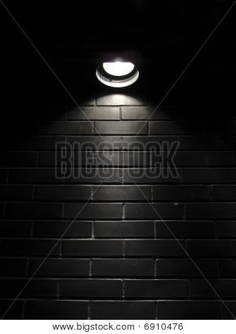 Spotlight On A Black Brick Wall