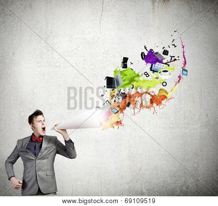 Young businessman speaking in trumpet and colorful splashes flying out