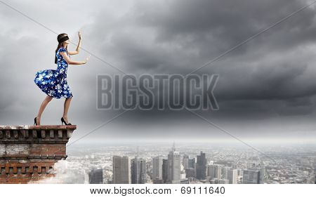 Young woman in blue dress walking on edge of roof