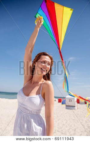 woman playing on the beach with colorful kite