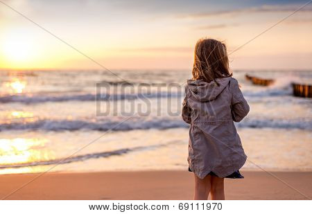 little daughter looking the sun dive in the  wide ocean