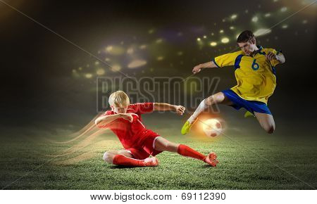 Two young football players struggling for ball