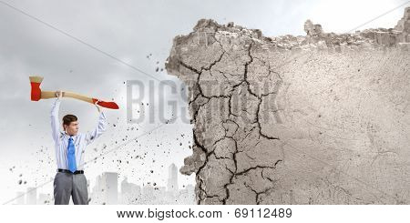 Young determined businessman with big axe in hands