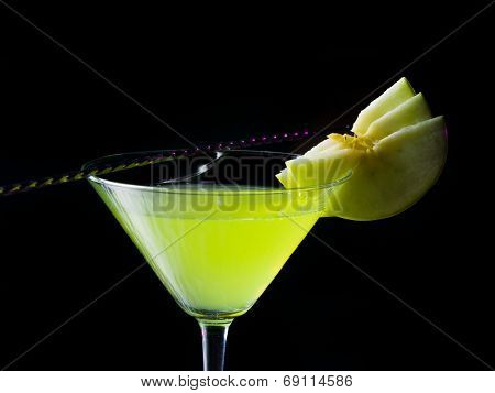 appletini cocktail with apples slices, vodka, pineapple juice, liqueur in classic martini cocktail glass