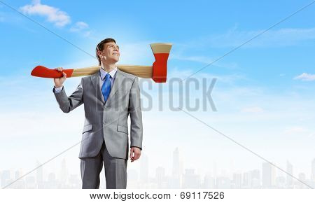 Young businessman holding big axe on shoulder