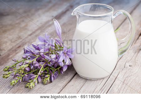 Milk Jug And Bluebell Flowers Bunch On Wooden Rustic Board