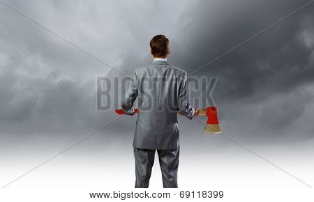 Rear view of young determined businessman with axe in hands