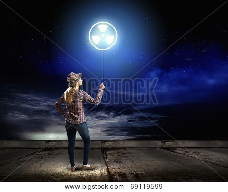 Rear view of woman holding balloon with radioactivity sign