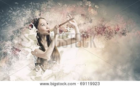 Young pretty asian woman in dress playing fife