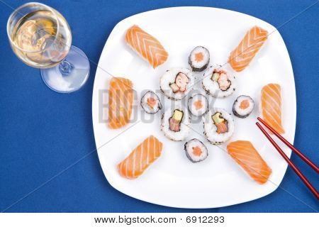 Sushi plate with glass of wine on a blue background