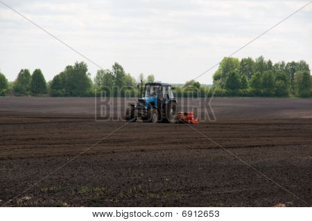 Tractor cultivating potato field (rural scene)