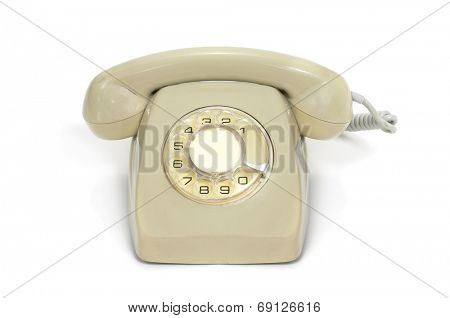 a beige old rotary dial telephone on a white background