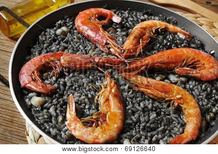 closeup of spanish arroz negro, a typical rice casserole made with squid ink