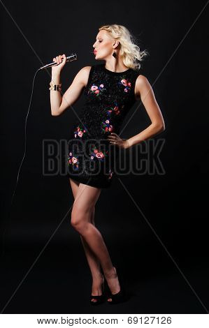Full-length portrait of beautiful singing woman with microphone. Singer. Karaoke song
