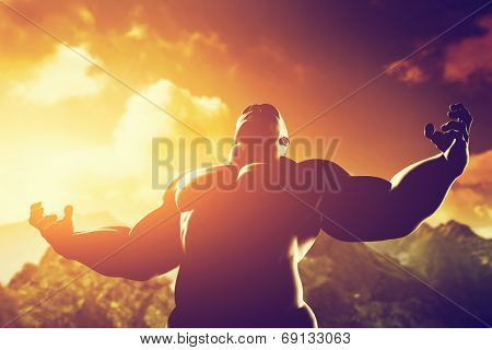 Very muscular strong man with hero, athletic body shape expressing his power and strength on the peak of the mountain at sunset