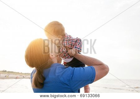 Young father holding his child up in the air on the beach and kissing with love. Son and parent bond