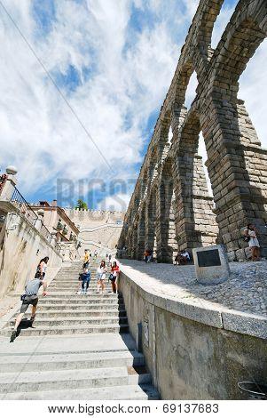 Tourist Climb On Ancient Aqueduct Of Segovia