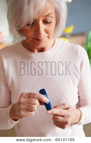 Senior Female Diabetic Checking Blood Sugar Levels
