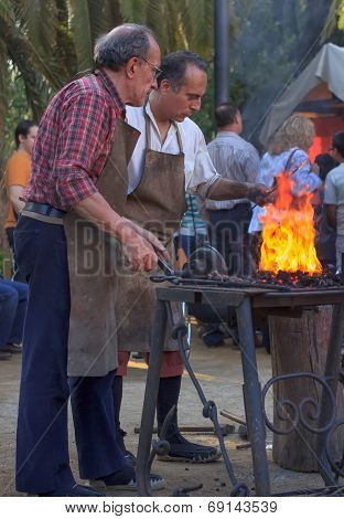 Blacksmiths Working On Metal