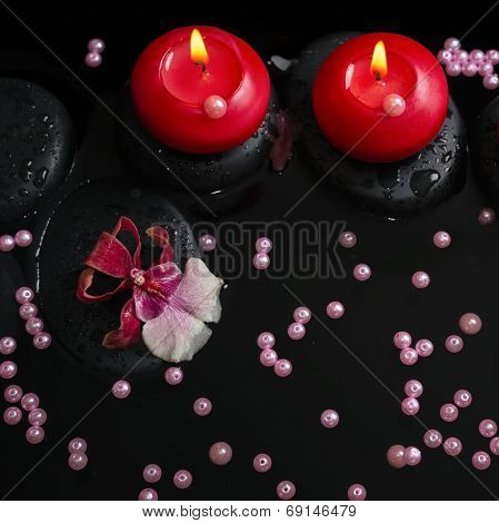 Spa Concept Of Red Candles On Zen Stones With Drops, Orchid Cambria Flower And Pearl Beads In Reflec