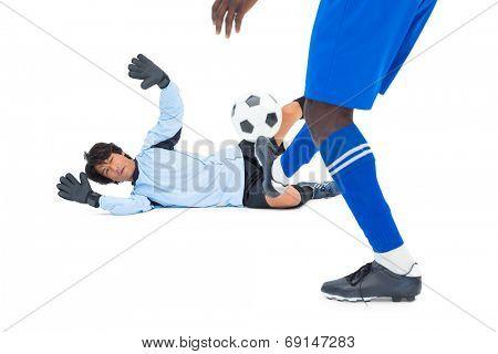 Striker hitting football at goalkeeper on white background