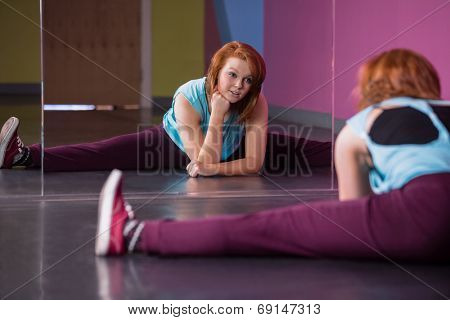 Pretty break dancer doing the splits looking in mirror in the dance studio