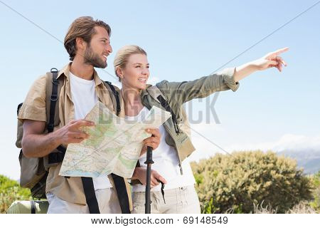 Attractive hiking couple reading the map on mountain trail on a sunny day
