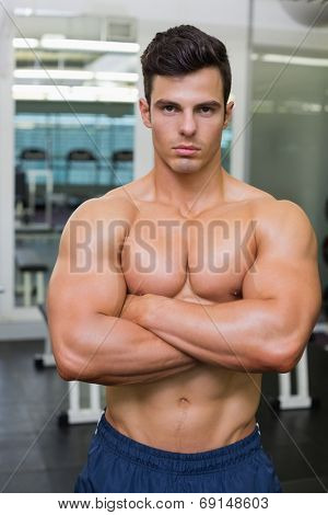 Serious shirtless young muscular man standing in gym