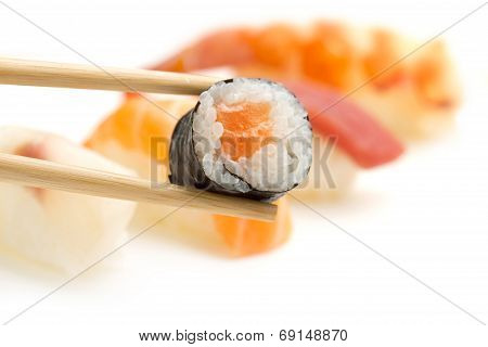 chopsticks with salmon sushi roll