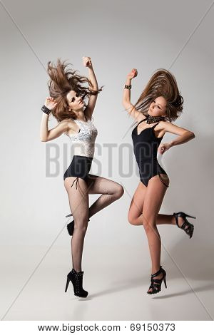 Go-go dancing women posing against gray