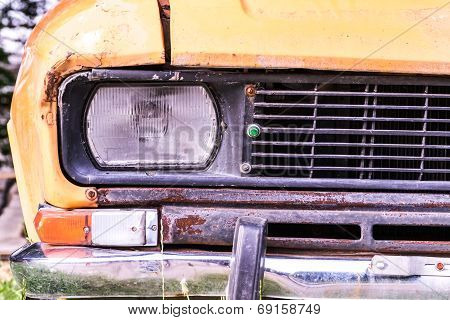 Headlamp and grille of old rusted car closeup
