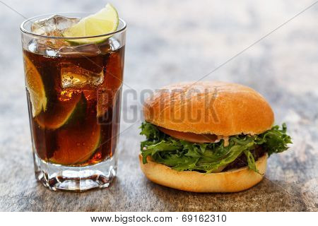 Fastfood, unhealthy. Tasty burger with drink on the table