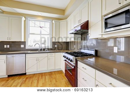 White Kitchen With Burgundy Stove And Grey Counter Tops