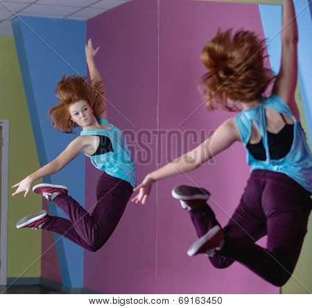 Pretty break dancer jumping up and looking in mirror in the dance studio
