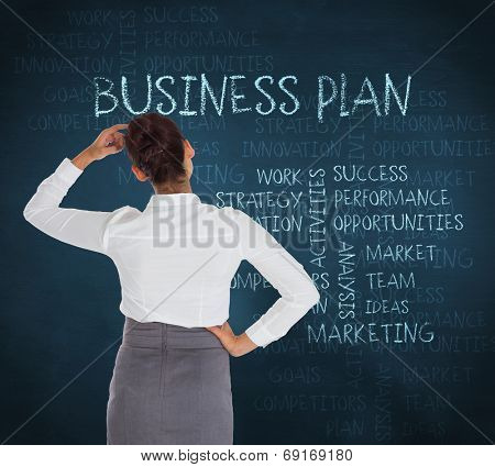 Businesswoman scratching her head against blue chalkboard with business buzzwords