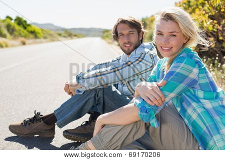 Attractive couple sitting on the road smiling at camera on a sunny day