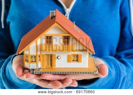 Close-up of hands holding miniature house model