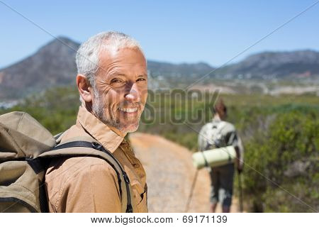 Hiking couple walking on mountain trail man smiling at camera on a sunny day
