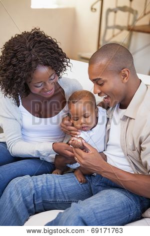 Happy parents spending time with baby on the couch at home in the living room